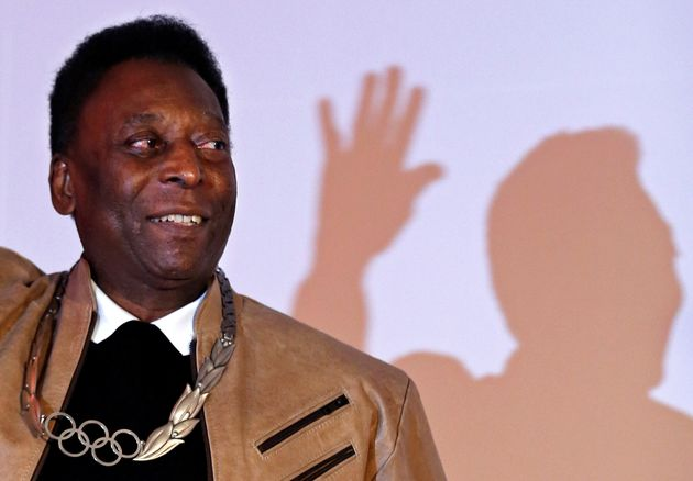 Brazilian soccer legend Pele poses for picture after receiving an Olympic necklace from President of...