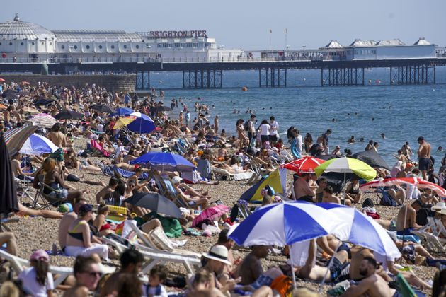 People enjoy the warm weather at Brighton beach in West Sussex.