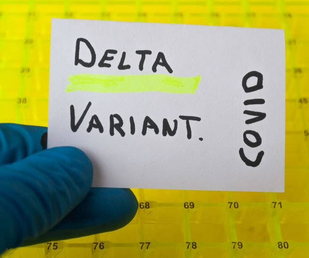 hand with a blue surgical glove holding a sign with the text delta variant in a