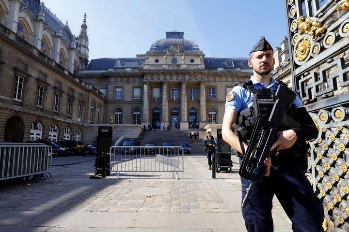 French police stand guard in front of the courthouse on the Ile de la Cite ahead of the opening of the trial of the 2015 Pari