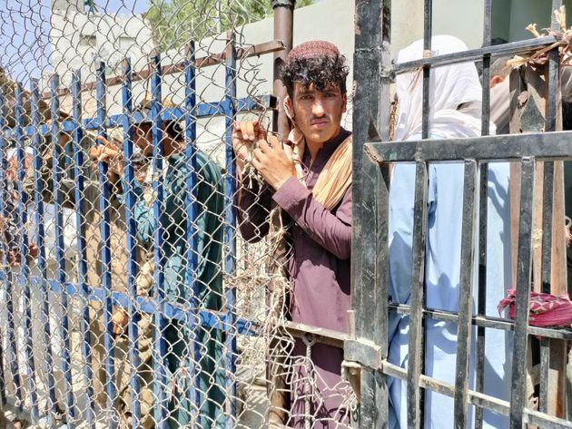 Un hombre afgano espera, junto con otras personas, en el puesto fronterizo de Torkham para cruzar a Pakistán...