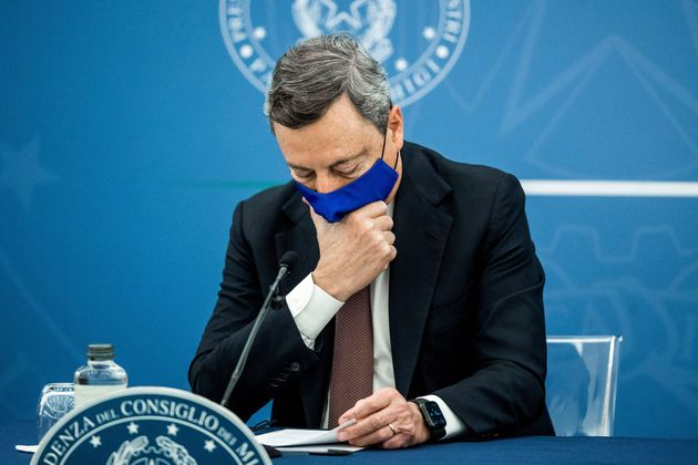 TOPSHOT - Italian Prime Minister Mario Draghi touches his face mask during a press conference with Italy's...