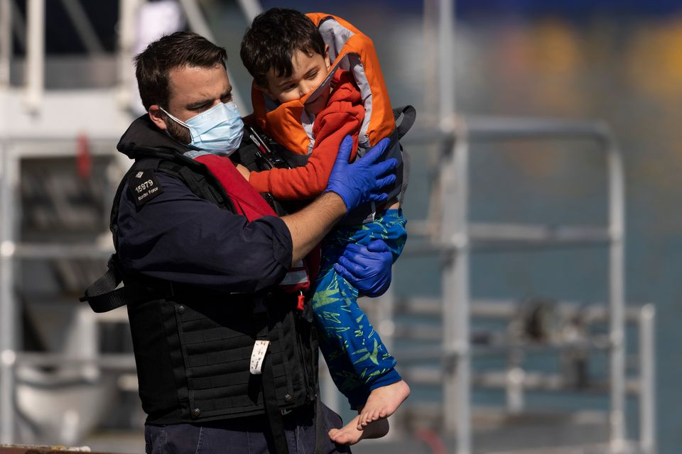A young migrant being carried by a Border Force official after arriving into Dover on