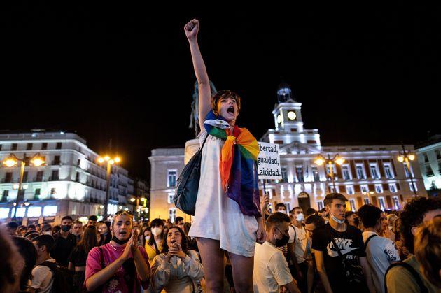 Una mujer alza el puño en Sol (Madrid) ataviada con la bandera arcoiris, este viernes, tras conocerse...