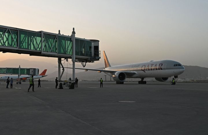 Members of ground staff stand on the tarmac as a Qatar Airways aircraft taxis before taking off from the airport in Kabul on