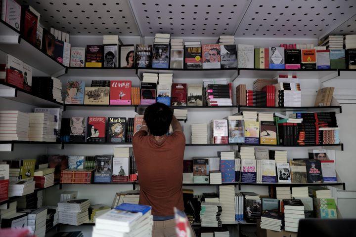 Un librero colocando ejemplares en la Feria del Libro de Madrid 2021.