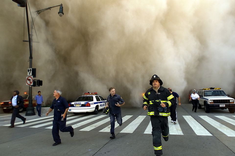 Policemen and firemen run away from the huge dust cloud caused as the World Trade Centre
