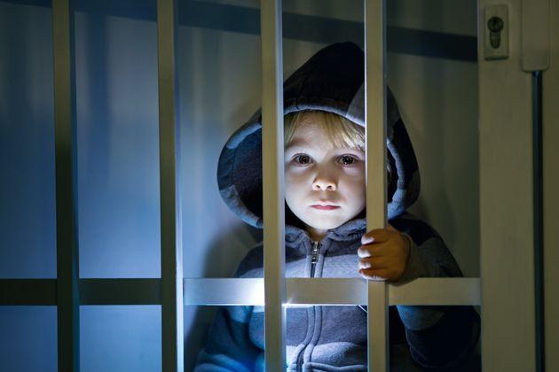 Small toddler child, blond boy, standing locked behind bars, child punishment, sad