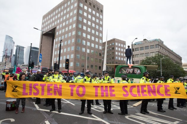 Environmental activists from Extinction Rebellion hold a banner calling on the government to cease all...