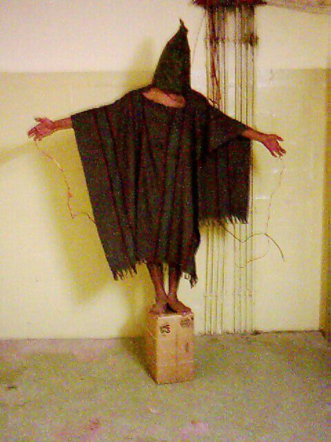 An unidentified detainee is forced to stand on a box with a bag over his head and wires attached to him in late 2003 at the A