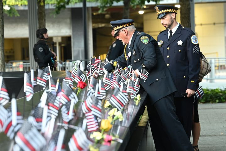 Retired Illinois Willow Springs Police Chief Sam Pulia and his nephew, Chicago Police Sgt. Daniel Pulia, place flags at the S
