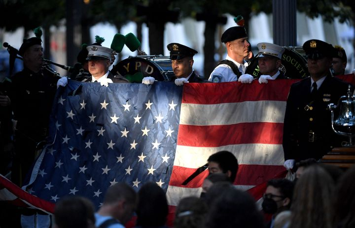 New York police and firefighters hold a U.S. flag as a band plays the US National Anthem at the National 9/11 Memorial during