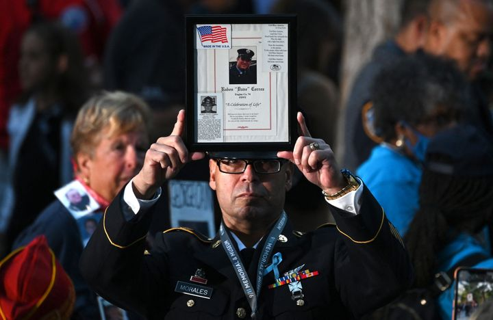 A firefighter holds up the image of a 9/11 victim as people attend a ceremony commemorating the 20th anniversary.