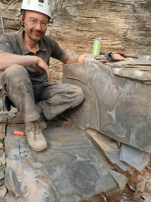 ティタノコリスの化石の上に座る、ジーン=バーナード・キャロン氏