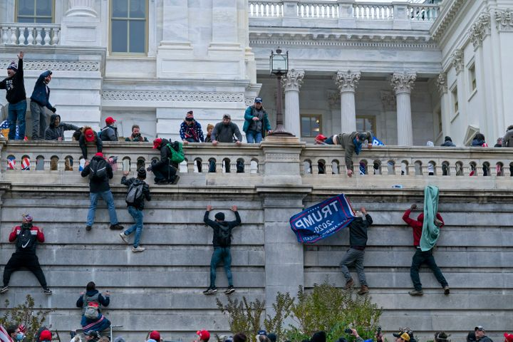 Rioters climb the west wall of the the U.S. Capitol in Washington during the Jan. 6 attack.