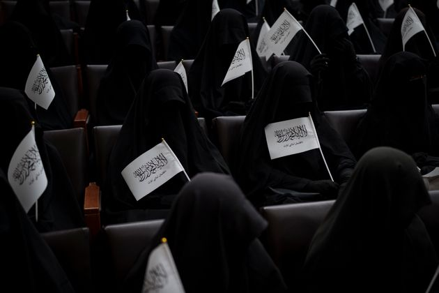 Women wave Taliban flags as they sit inside an auditorium at Kabul University's education center during...
