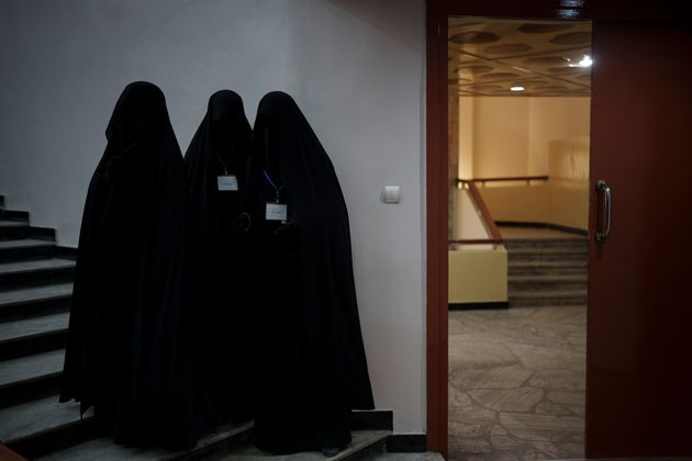 Women stand inside an auditorium at Kabul University's education center during a demonstration in support...