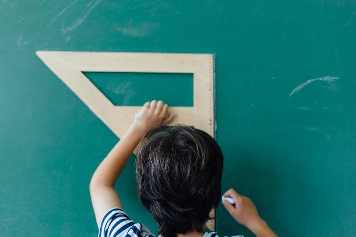 Close up of boy using wooden ruler on blackboard.