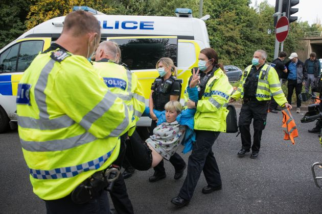 Police officers arrest an Insulate Britain climate activist who had been blocking a slip road from the...