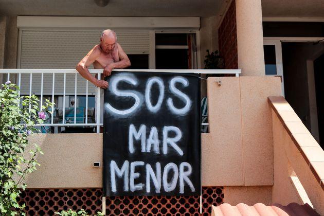 Un hombre cuelga un cartel en su casa con el mensaje 'SOS Mar Menor', en La Manga del Mar Menor (Murcia),...