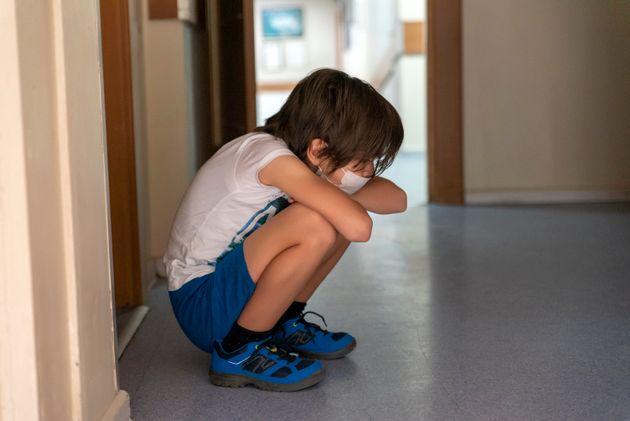 boy waiting sadly in hospital corridor