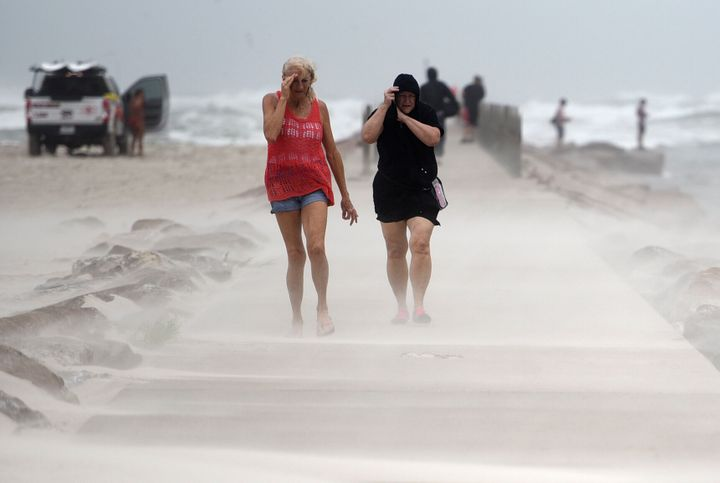 People shield their faces from wind and sand ahead of Tropical Storm Nicholas, Monday, on the North Packery Channel Jetty in