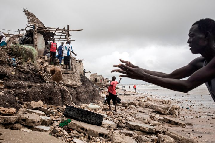A man repairs his makeshift barrier to protect his house before the next high tide arrives in Bargny, Senegal, on Sept. 3, 2020.