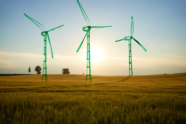 Digital generated image of hand drawn wind turbines overlaid over landscape. Sustainable energy