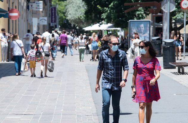 Una pareja camina con su mascarilla en
