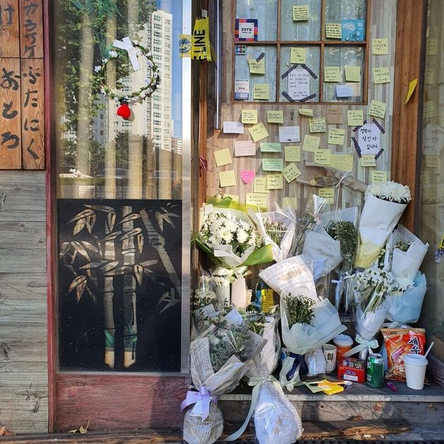 지난 7일 숨진 채 발견된 자영업자 ㄱ(57)씨가 운영하던 서울 마포구의 맥줏집 문 앞에 17일 오후 ㄱ씨를 추모하는 포스트잇과 조화가 놓여 있다. 정유경 기자