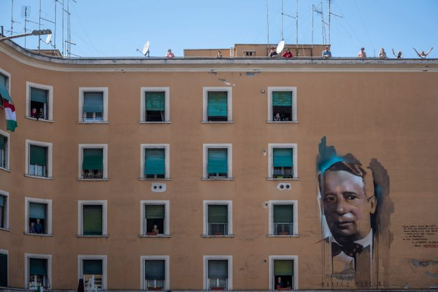 ROME, ITALY - APRIL 25: People stand at their windows and balconies to take part in a 'Liberation Day'...