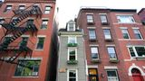 Boston's famous Skinny House, middle, is seen, Friday, Aug. 13, 2021, and is on the market for $1.2 million. This is the first time the vertically rectangular-shaped house has been on the market since 2017 when it was sold for $900,000. The home, located in Boston's North End, is about 1,165 square feet and is barely 10 feet wide at its widest point. (AP Photo/Elise Amendola)