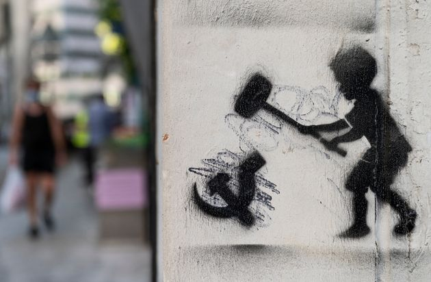 HONG KONG, CHINA - 2020/08/05: A graffiti is seen depicting a child hammering the communism symbol in...