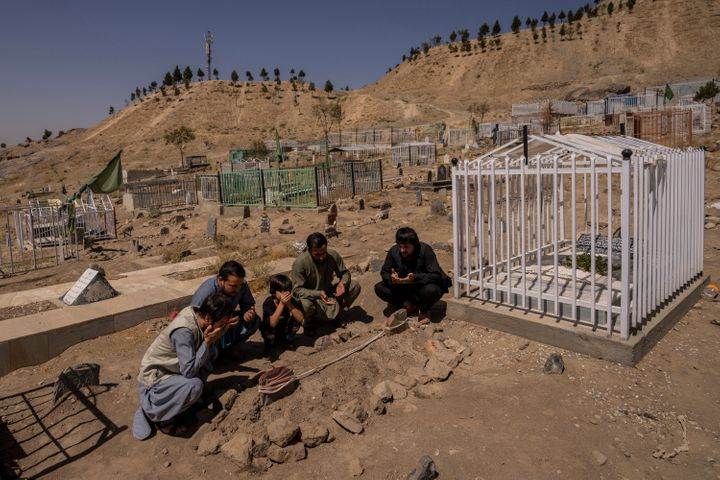 The Ahmadi family prays next to graves of family members killed by a U.S. drone strike in Kabul.