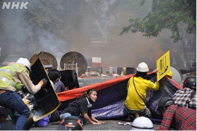 迫りくる警察と軍と防火膜の下に身を伏せるエンジェルさん(マンダレーにて3月3日に市民撮影)