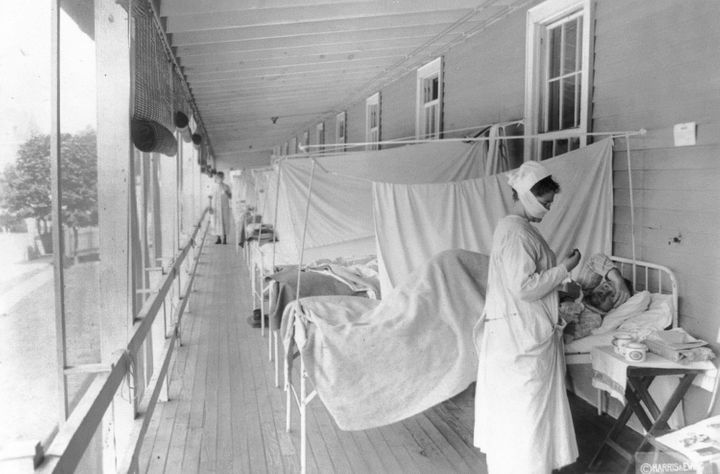 In this November 1918 photo made available by the Library of Congress, a nurse takes the pulse of a patient in the influenza ward of the Walter Reed hospital in Washington. (Harris & Ewing/Library of Congress via AP, File)