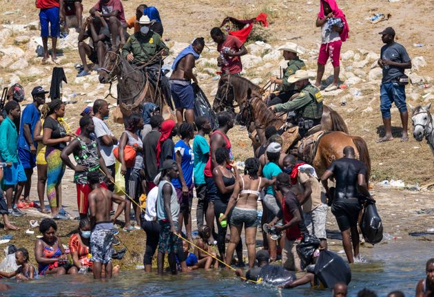 US border patrol agents interact with Haitian immigrants on the bank of the Rio Grande in Del Rio, Texas...
