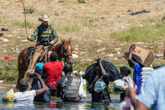 A US Border Patrol agent on horseback uses the reins as he tries to stop Haitian