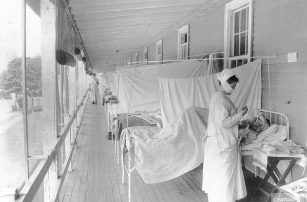 Σε αυτή τη φωτογραφία από τον Νοέμβριο του 1918, μια νοσοκόμα παίρνει τον παλμό ενός ασθενούς στο τμήμα...