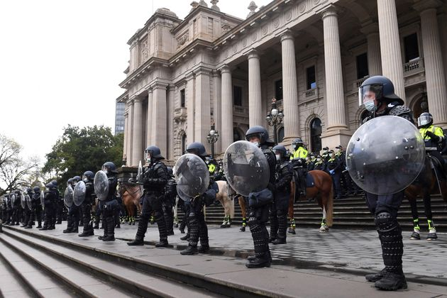 Riot police guard Victoria's Parliament House as construction workers and far right activists protest...
