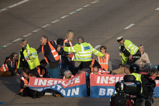 Surrey Police officers try to remove Insulate Britain climate activists from the