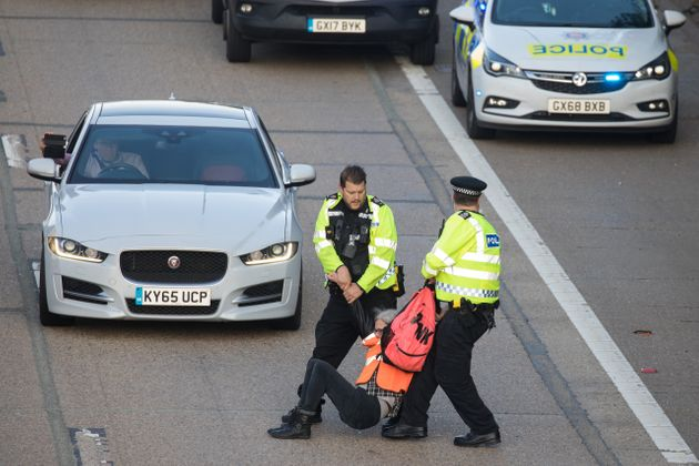 Surrey Police officers haul an Insulate Britain climate activist from the carriageway of the