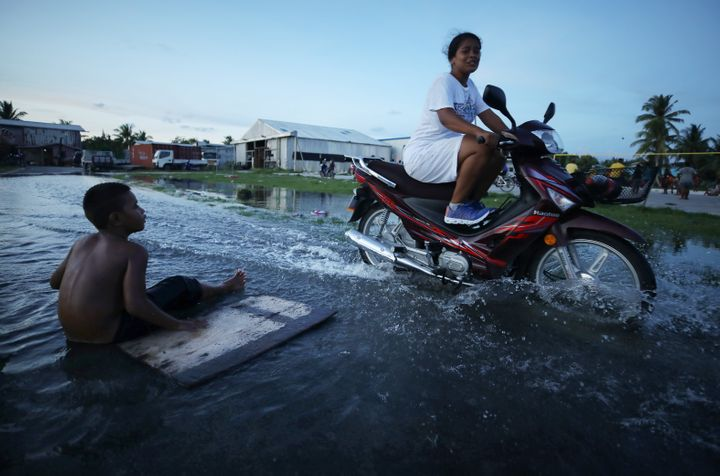 """A woman rides her scooter through floodwaters occurring around high tide in a low-lying area near the airport in 2019 in Funafuti, Tuvalu. The South Pacific island nation of about 11,000 people has been classified as """"extremely vulnerable"""" to climate change by the United Nations Development Program."""