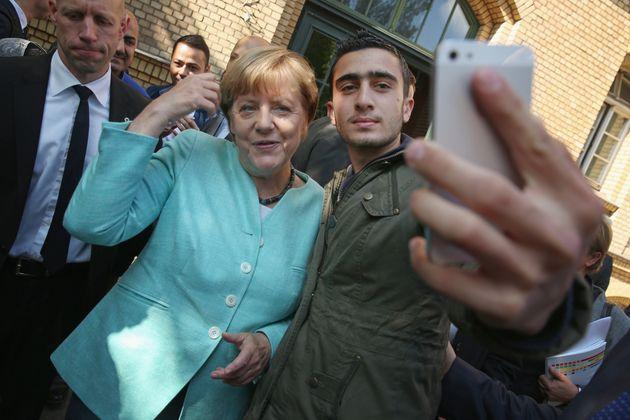 Le 10 septembre 2015, Angela Merkel est photographiée avec le réfugié syrien Anas...