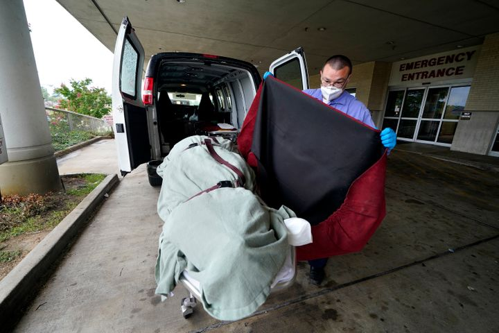 In this Aug. 18, 2021, file photo, an employee of a local funeral home covers the body of a COVID-19 patient patient who died as he prepares to take it away from a loading dock, at the Willis-Knighton Medical Center in Shreveport, La. (AP Photo/Gerald Herbert, File)