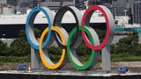 A boat (R) prepares to tow a barge containing the giant Olympic Rings as they are removed from the waterfront area at Odaiba Marine Park after the Tokyo 2020 Olympic Games came to an end on August 8 in Tokyo on August 11, 2021. (Photo by KIM KYUNG-HOON / POOL / AFP) (Photo by KIM KYUNG-HOON/POOL/AFP via Getty Images)