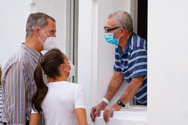 Los reyes Felipe VI y Letizia conversan con un vecino mientras visitan este jueves en el acuartelamiento...