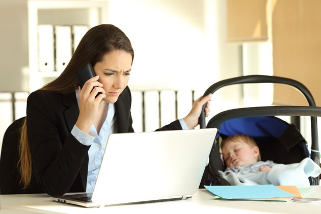 Stressed mother working attending a phone call and taking care of her baby at