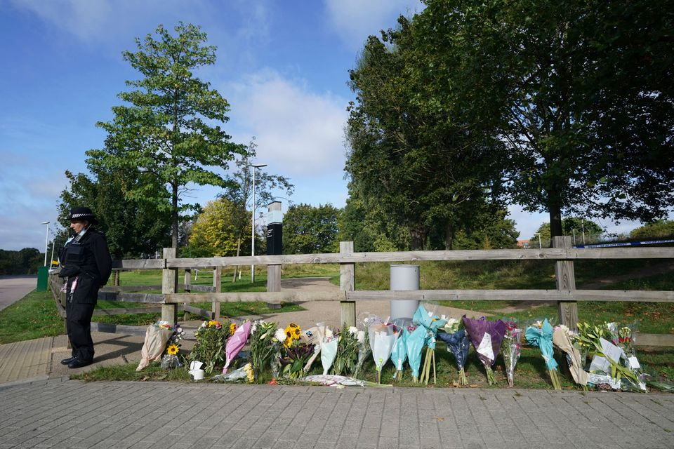 A police officer stands by floral tributes at Cator Park in Kidbrooke, near to the area where the body...