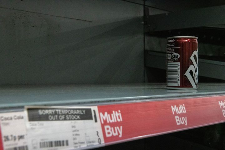 One remaining can of soft drink on a near-empty shelf at Asda